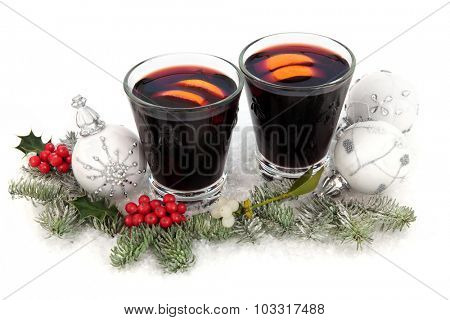 Christmas mulled wine on snow with bauble decorations, holly, mistletoe and winter greenery on snow over white background.
