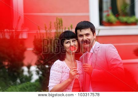 Joyful Couple Having Fun With Moustache In The Park