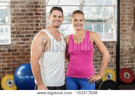 Crossfit couple smilling at the camera in crossfit gym