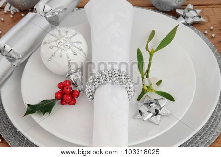 Christmas holiday dinner place setting with plates, napkin,  bauble decorations, holly and mistletoe over oak background.