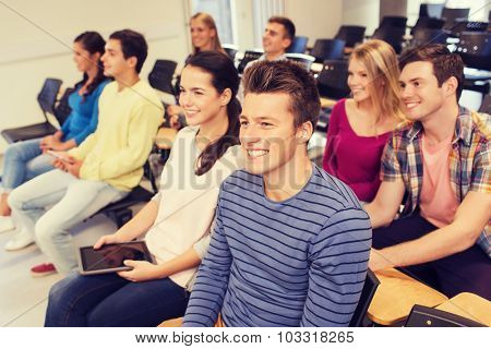education, high school, teamwork and people concept - group of smiling students with tablet pc computers sitting in lecture hall