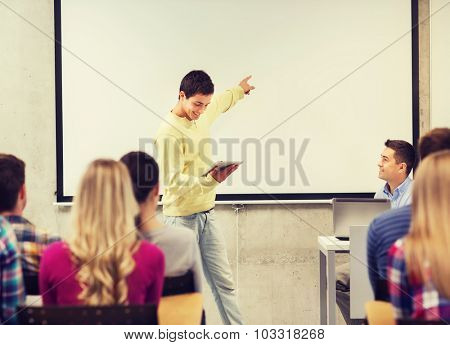 education, high school, technology and people concept - smiling student boy with tablet pc, laptop computer standing in front of classmates and teacher in classroom