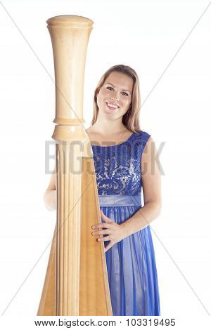 Young Caucasian Woman Stands With Concert Harp In Studio Against White Background
