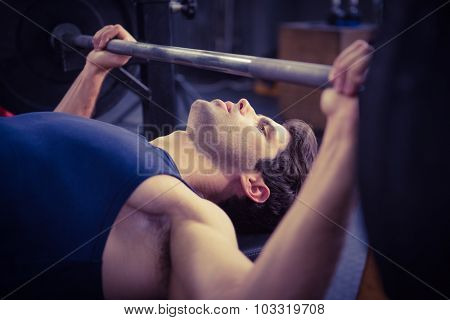 Side view of a man holding barbell at the gym