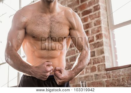Midsection of a shirtless man showing his body at the gym