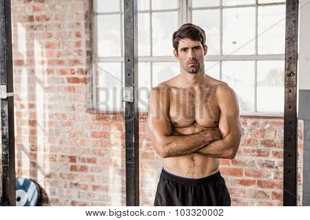 Portrait of a shirtless man with arms crossed at the gym