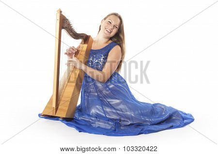 Young Caucasian Woman In Blue Dress Sits On Floor With Small Harp In Studio Against White Background