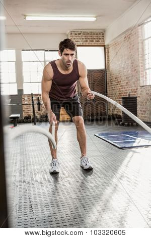 Man exercising with battling rope at the gym