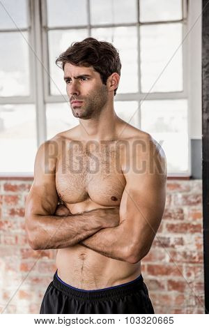 Shirtless man with arms crossed at the gym