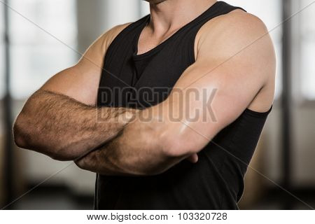 Midsection of man with arms crossed at the gym