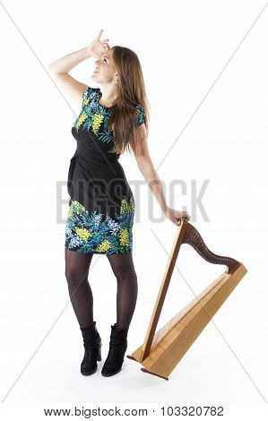 Young Caucasian Woman Stands With Small Harp In Studio Against White Background