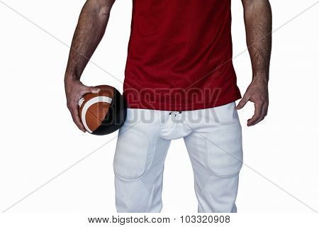 Midsection of a rugby player holding ball against white background