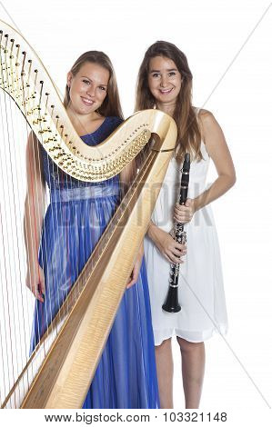 Two Young Women In Studio With Harp And Clarinet Against White Background