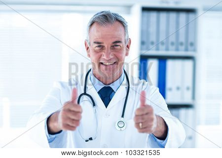 Portrait of smiling male doctor showing thumps up sign in clinic
