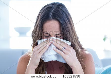 Sick woman sneezing in tissue at home