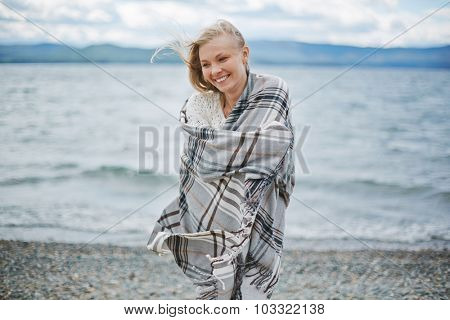 Young woman wrapped in plaid standing by the seaside