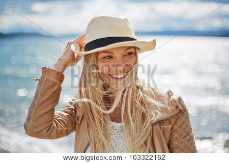 Blond girl in hat spending leisure by the seaside