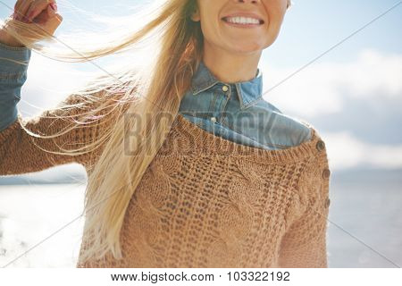 Blond girl with long hair and toothy smile showing satisfaction