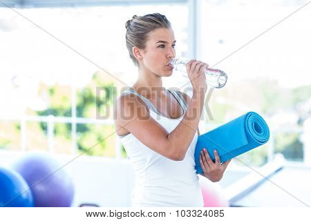 Beautiful woman drinking water while holding yoga mat in fitness studio