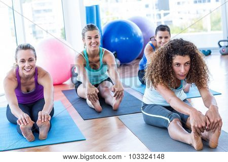 Woman sitting in forward bend pose in fitness studio