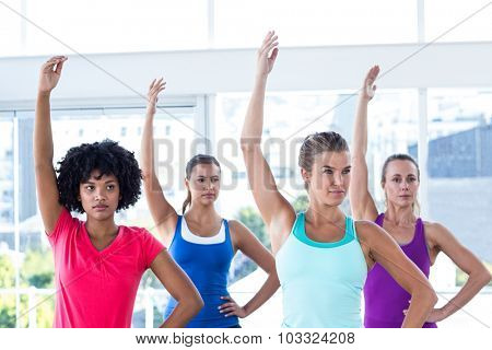 Focused woman in fitness studio with left arm raised while standing