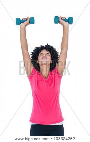 Young woman exercising with dumbbells against white background