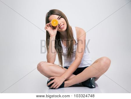 Portrait of a cheerful girl sitting on the floor and covering one eye with orange isolated on a white background