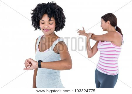 Fit woman checking time on wristwatch while female friend exercising against white background