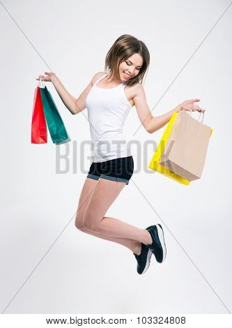 Full length portrait of a happy girl jumping with shopping bags isolated on a white background