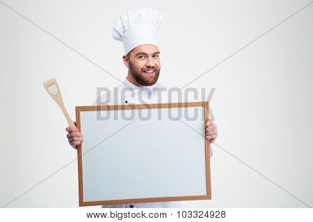 Portrait of a smiling male chef cook holding blank board isolated on a white background