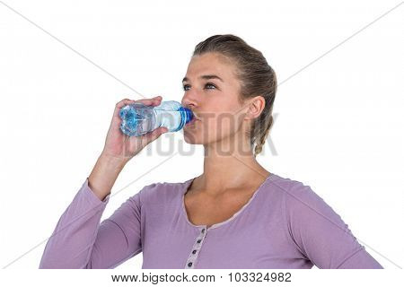 Close-up of young beautiful woman drinking water against white background