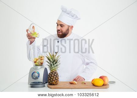 Portrait of a happy male chef cook using blender with fruits isolated on a white background