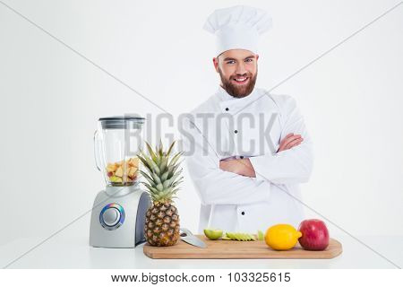 Portrait of a smiling chef cook standing with arms folded near table with fruits isolated on a white background