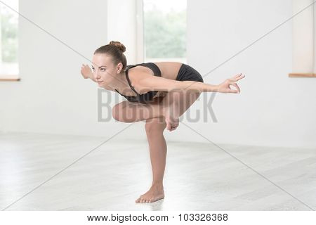Full length portrait of a young woman doing yoga exercises in gym