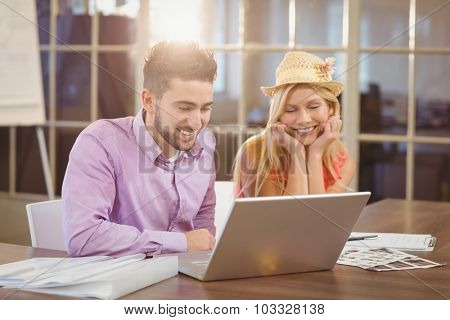 Smiling business woman wearing hat sitting by male colleague looking at laptop in creative office