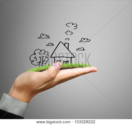 Businessman holding a house model
