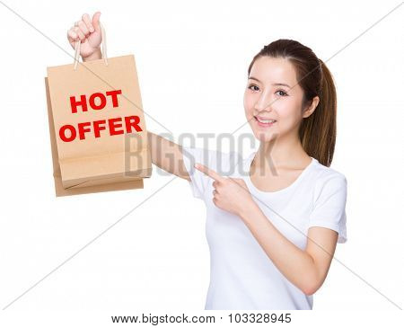 Woman finger point to shopping bag and showing phrase of hot offer