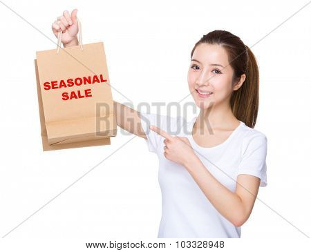 Woman finger point to shopping bag and showing phrase of seasonal sale