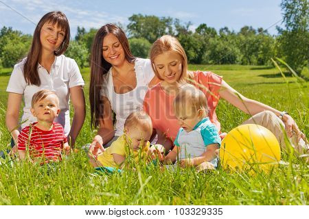 Three beautiful happy mothers with babies sitting