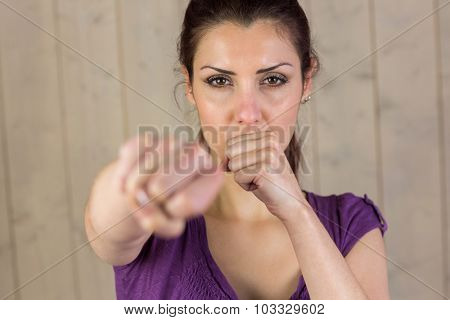Portrait of beautiful woman punching while standing by wall