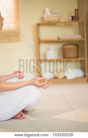 Cropped woman in yoga pose while sitting on floor