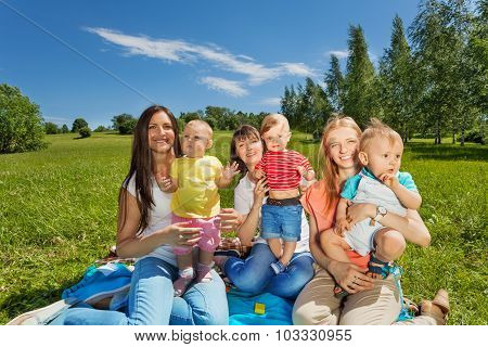 Three happy mothers holding cute babies in park