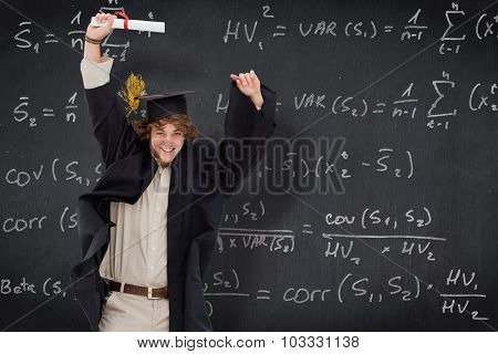 Male student in graduate robe jumping against blackboard