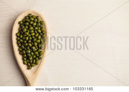 Wooden spoon of green lentils on wooden table