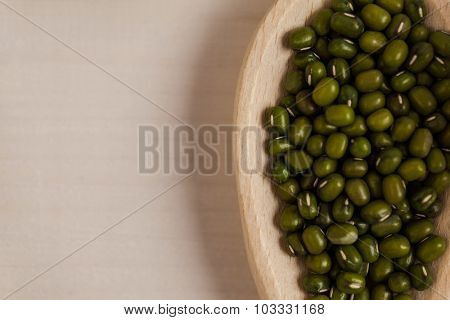 Portion cup of green lentils on wooden table