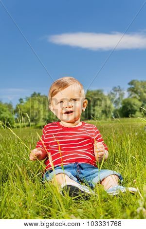 Smiling baby sitting on the green grass alone
