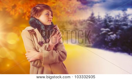 Thoughtful woman in winter coat against autumn changing to winter