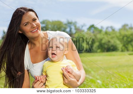 Happy mother with child in the green meadow