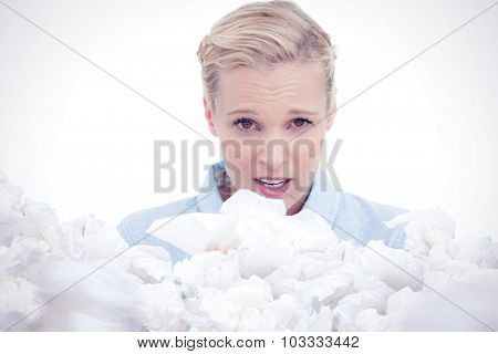 Blonde sick woman holding lots of tissues against used tissues