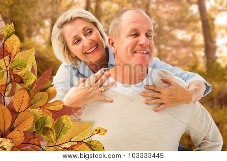 Happy mature man giving piggy back to partner against tranquil autumn scene in forest